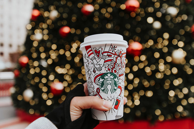 person holding white Starbucks cup in front of Christmas tree