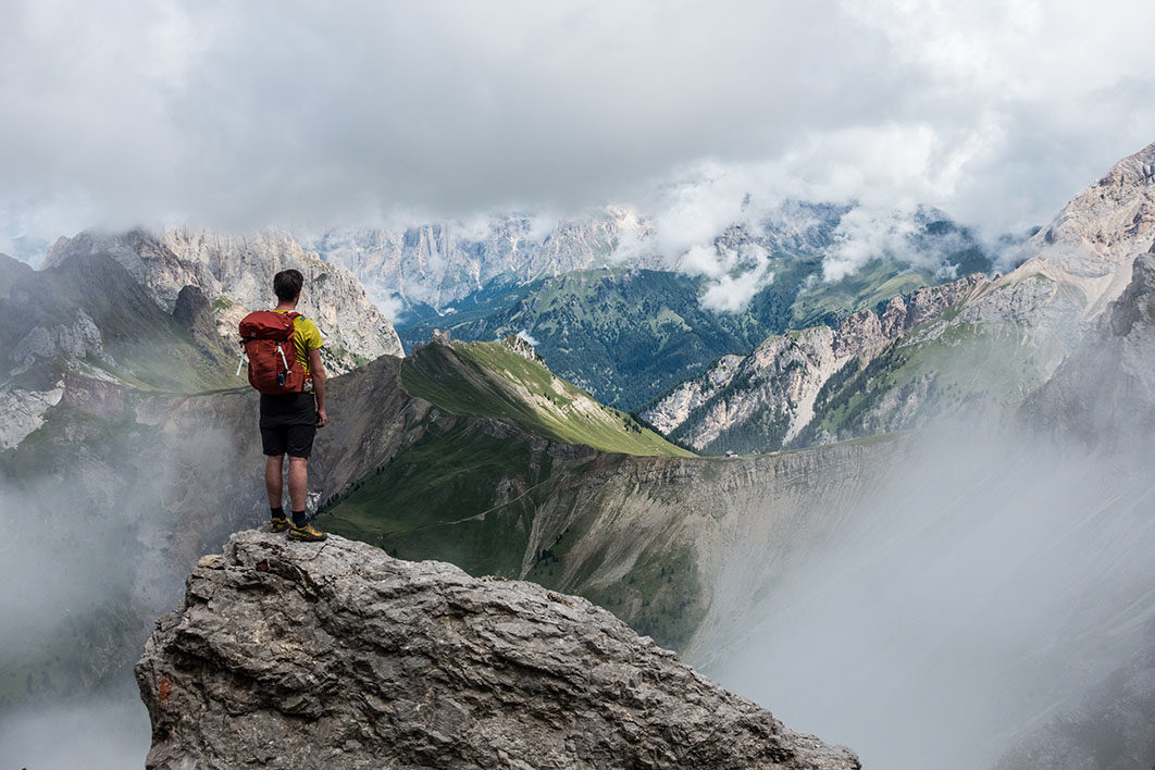hiker on cliff looking over valley and mountains